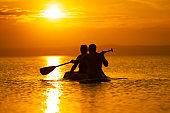 active seniors paddling into sunset