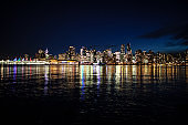 Reflecting water surface at downtown Vancouver, view from Stanley Park at night