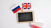 British and Russian flags. Small whiteboard with chalk. Top view on a white background. Mockup, copy space