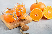 Homemade pumpkin and orange jam in a jars on a gray concrete background.