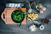 A table when preparing a meal. Green arugula in a black bowl, feta cheese, dried tomatoes for preparing a rocket salad.