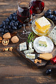 Cheese plate with grapes, honey, nuts and red wine on a wooden table.