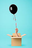 A hand from a cardboard box holds a black balloon