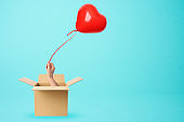 A hand from a cardboard box holds a red heart-shaped balloon