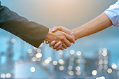 Close-up of two business partners standing and shaking hands they greeting each other during a meeting hand together is a collaborative concept of teamwork for business partners.