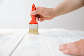 A man paints a wooden board with white paint. The concept of DIY and renovation of new things.