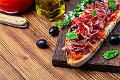 Delicious bread toast with natural tomato, extra virgin olive oil, Iberian ham, black olives and basil leaves. On wooden background.