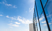 Cloud sky reflected on glass windows of modern building