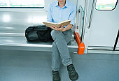 Businessman reading a book in subway train