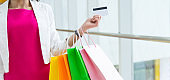 Young woman holding a credit card and colorful shopping bags