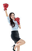 Businesswoman arms raised with boxing gloves on white background