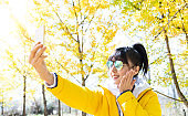 Woman taking selfie under yellow ginkgo trees