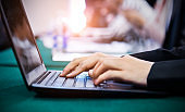 Business people typing on laptop keyboard at conference