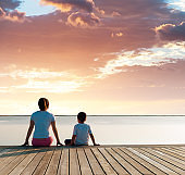 Mother with her son enjoying lake view at sunset