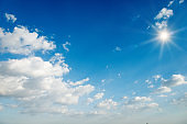 Sun with sunlight on blue sky and clouds