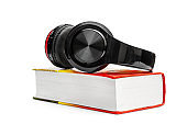Headphones with book on white. Audio Books concept.