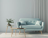 Living room with a blue sofa and a stylish wooden tables. 3d render