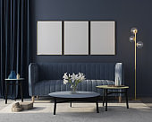 Mock up Interior of the living room in monochrome blue with three posters. 3d render