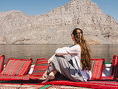 Fashionable woman sitting in a boat. Oman Fjords