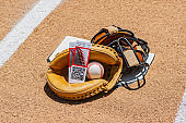 A pair of game ticket stubs in a catcher's mitt with mask at home plate