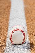 Low view of baseball on Foul Line on dirt of baseball diamond