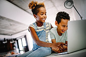 Kids, technology concept. Happy children using laptop to learn, play, fun.