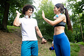 Happy young people jogging and exercising in nature