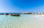 Boat in blue sea and white sand beach.