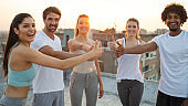 Group of young happy people friends exercising outdoors at sunset.