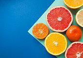 Many citrus fruits on blue background.