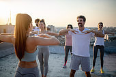 Group of fit healthy friends, people exercising together outdoor on rooftop