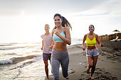 Group of friends running at the beach on beautiful summer sunset