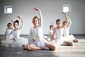 Little ballerinas in ballet studio. Group of happy girls exercising together