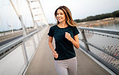 Portrait of fit and sporty young woman jogging outdoor