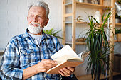 Senior man at home reading book and enjoying retirement, penison