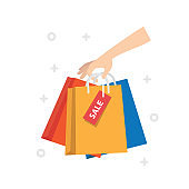 Female hand holding colorful shopping bags. Many packets with in woman's arms. Black friday sale concept