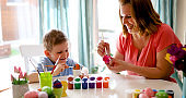 Happy young mother and son are painting Easter eggs