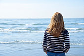 Rear view shot of woman standing on the beach