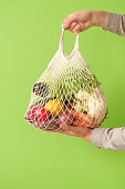 Male hand holding a white string shopping bag with vegetables and fruits  in front of a green background