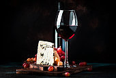 Port wine and blue cheese, still life in rustic style, vintage wooden table background, selective focus