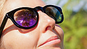 Woman wearing sunglasses with palms, sky reflection in mirror lens
