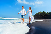 Young couple run by black sand beach along sea surf