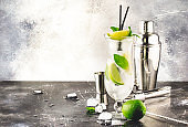 Lime caipirinha, classic Brazilian alcoholic cocktail with cane vodka cachasa, sugar syrup, lime juice and crushed ice in tall glass on gray table, bar tools, place for text
