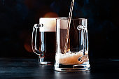 Two glasses of german light beer, beer poured into mug, dark bar counter