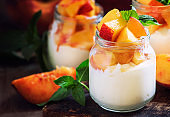 Dessert with sweet peaches, cottage cheese and whipped cream, served in glass jars, vintage wooden background, selective focus