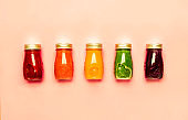 Multicolored detox vegan vegetable juices and smoothies in glass bottles on pink table, raw diet and clean food concept, drink background, copy space, top view