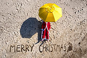 Aerial view of Santa Claus and Merry Christmas written on the sand by the sea