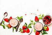 Strawberry dairy smoothies with jam, berry and green mint, white background, top view