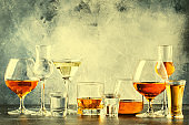 Selection of hard strong alcoholic drinks in big glasses and small shot glass in assortment: vodka, cognac, tequila, brandy and whiskey, grappa, liqueur, vermouth, tincture, rum.