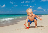 Happy baby boy digging sand on sunny tropical beach